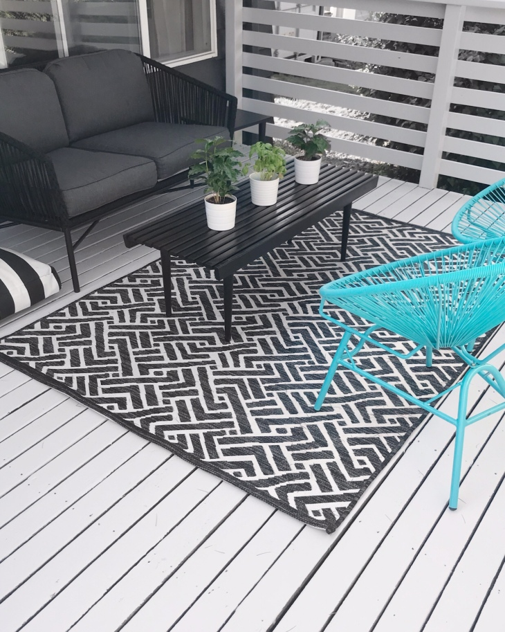 Black and white modern outdoor patio with turquoise acapulco chairs